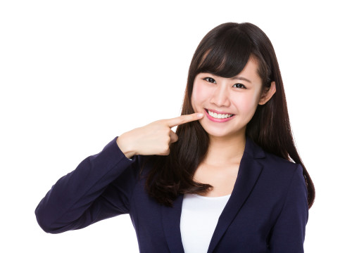 Businesswoman with finger point to her teeth