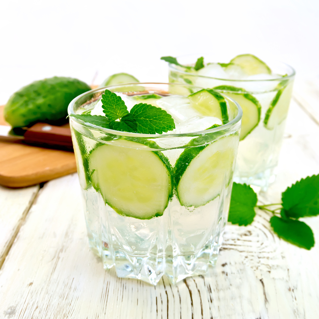Lemonade with cucumber and mint in two glasses, a knife, a cucumber on the background light wooden boards