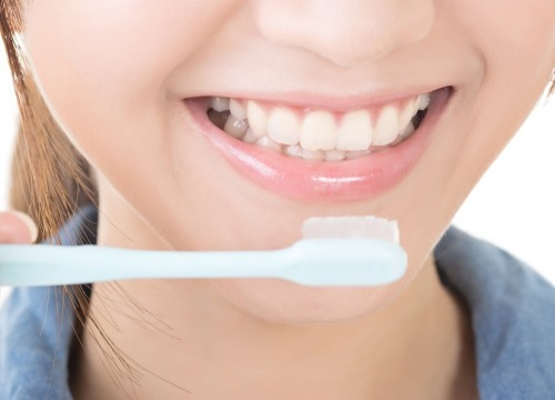 Closeup shot of woman brushing teeth. Profile view.