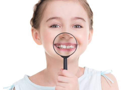 Close-up portrait of cute little girl showing teeth through a magnifying glass - isolated on white.