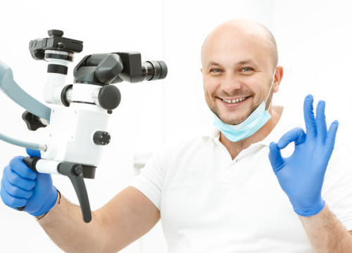 Dentist doing fine sign near the dental microscope in the clinic